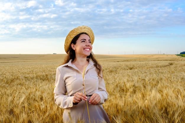 Jolie jeune femme aux cheveux longs dans un chapeau de paille tient une tige de blé dans un champ au lever du soleil et un sourire heureux. copier l'espace