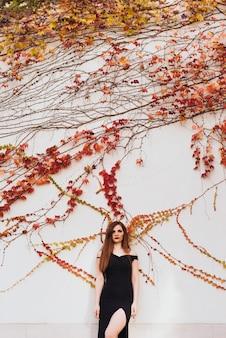 Jolie jeune femme aux cheveux longs en robe noire posant dans un parc près du mur, détendez-vous
