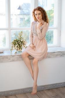 Une jolie jeune femme aux cheveux rouges dans une robe est assise sur le rebord de la fenêtre. il y a un bouquet de fleurs à côté. détente à la maison