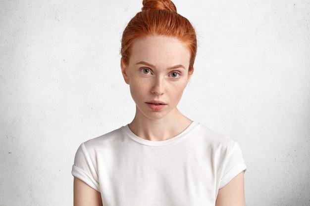 Jolie jeune femme aux cheveux rouges avec une peau tachetée de rousseur et un regard sérieux, vêtue d'un t-shirt blanc décontracté, des modèles contre un mur de béton blanc.