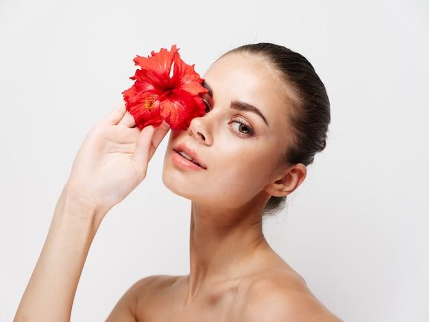 Jolie jeune femme aux épaules nues tenant une fleur rouge devant ses yeux sur une lumière