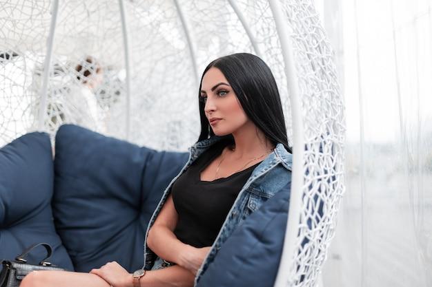 Jolie jeune femme aux longs cheveux noirs dans un t-shirt élégant dans une veste en jean bleu à la mode se détend à l'extérieur sur la terrasse d'un café d'été. modèle de jolie fille bénéficie de vacances dans la ville.