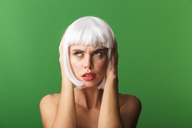 Jolie jeune femme aux seins nus bouleversée portant des cheveux blancs courts debout isolé, couvre les oreilles
