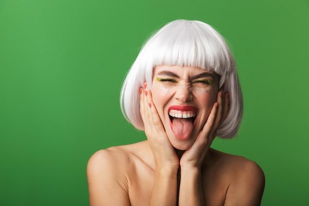 Jolie jeune femme aux seins nus portant des cheveux blancs courts debout isolé, collant sa langue