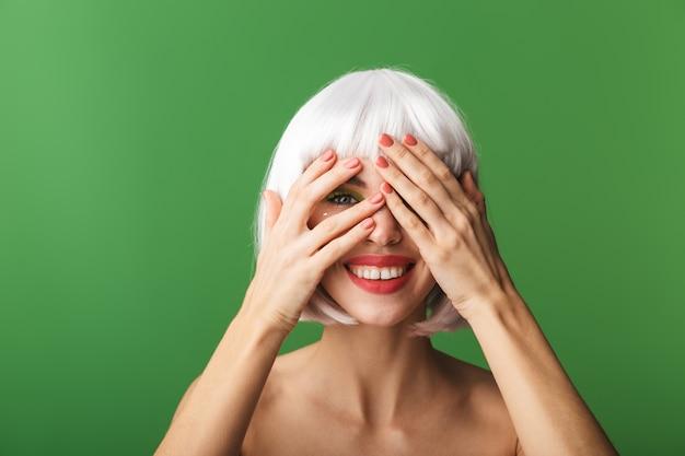 Jolie jeune femme aux seins nus portant des cheveux blancs courts debout isolé, couvre le visage avec les mains