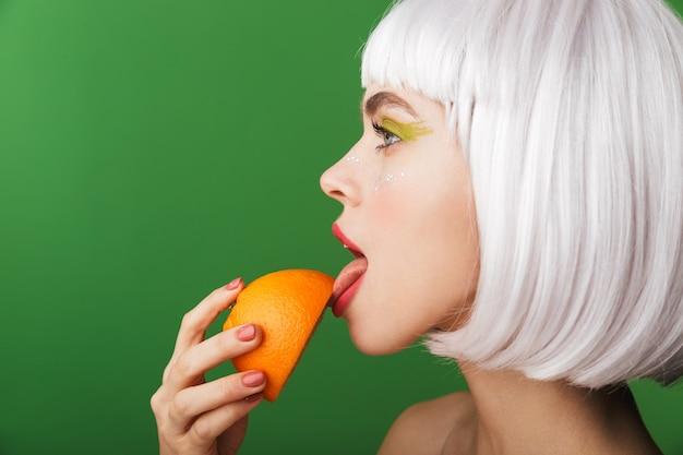 Jolie jeune femme aux seins nus portant des cheveux blancs courts debout isolé, manger des tranches d'orange