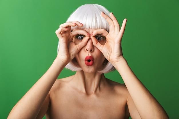 Jolie jeune femme aux seins nus portant des cheveux blancs courts debout isolé, montrant le geste ok