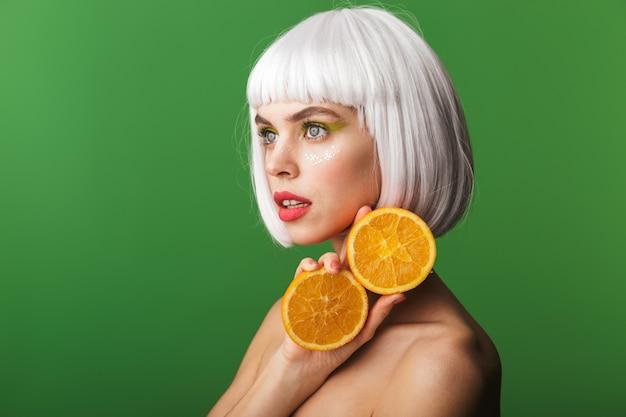 Jolie jeune femme aux seins nus portant des cheveux blancs courts debout isolé, montrant des tranches d'orange