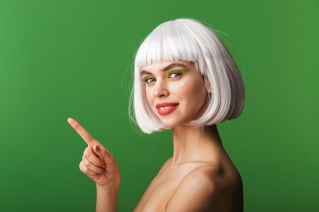 Jolie jeune femme aux seins nus portant des cheveux blancs courts debout isolé, pointant le doigt à l'espace de copie