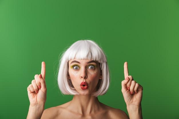 Jolie jeune femme aux seins nus portant des cheveux blancs courts debout isolé, pointant le doigt vers le haut à l'espace de copie