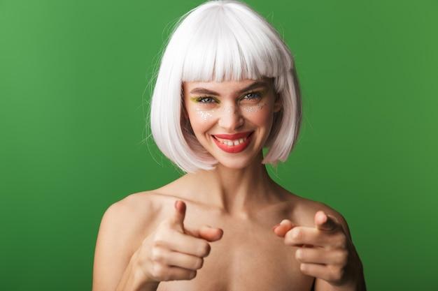 Jolie jeune femme aux seins nus portant des cheveux blancs courts debout isolé, pointant vers l'avant