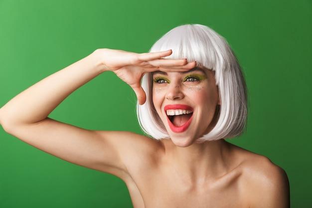 Jolie jeune femme aux seins nus portant des cheveux blancs courts debout isolé, à la recherche de loin