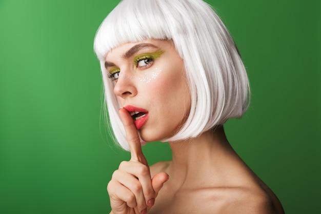 Jolie jeune femme aux seins nus portant des cheveux blancs courts debout isolé, regardant et montrant le geste de silence