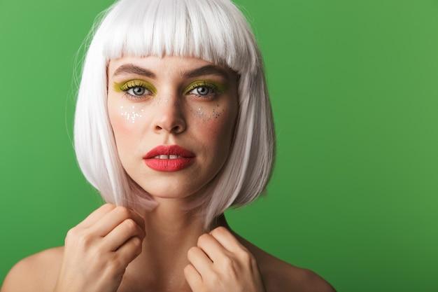 Jolie jeune femme aux seins nus portant des cheveux blancs courts debout isolé