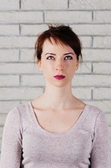 Jolie jeune femme aux yeux plissés et regardant vers le haut, la bouche fermée