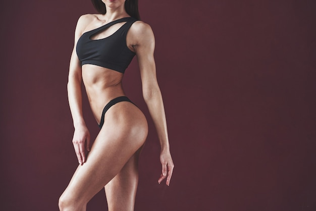 Jolie jeune femme avec une belle forme de corps de remise en forme posant dans la chambre