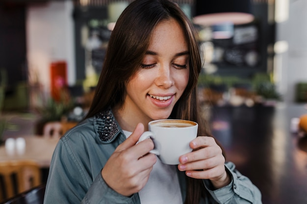 Jolie jeune femme bénéficiant d'une tasse de café