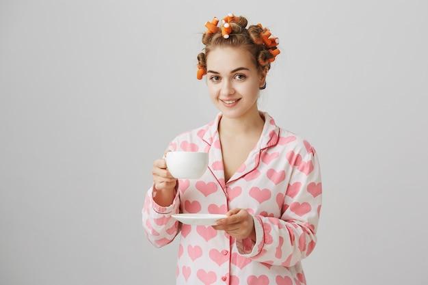 Jolie jeune femme en bigoudis et pyjamas buvant le café du matin