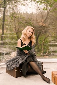 Jolie jeune femme blonde aux cheveux bouclés et maquillage avec un livre et une couverture dans une tente transparente dans la forêt