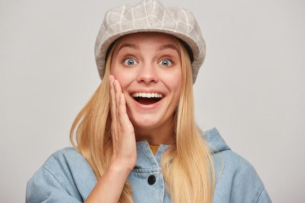 Jolie jeune femme blonde avec les cheveux vers le bas, à la joie heureux excité