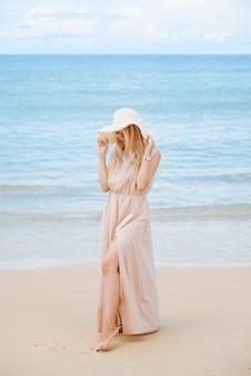 Une jolie jeune femme blonde dans un chapeau et une longue robe se dresse sur le sable blanc comme neige