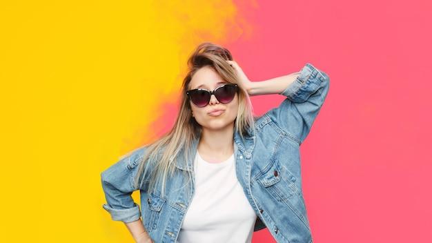 Une jolie jeune femme blonde élégante caucasienne pose en veste en jean sur fond jaune et rose