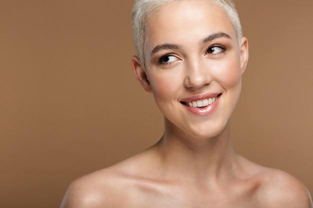 Une jolie jeune femme blonde élégante souriante avec une coupe de cheveux courte posant isolée sur un mur beige foncé.