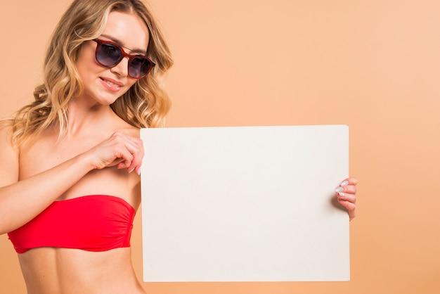 Jolie jeune femme blonde en haut tenant du papier vierge