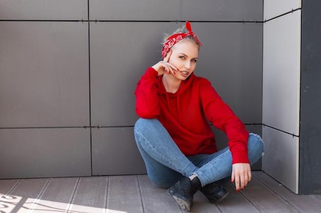 Jolie jeune femme blonde heureuse dans un bandana élégant avec un motif en jean bleu dans un sweat-shirt rouge à la mode en bottes noires au repos assis près d'un mur gris un jour d'été