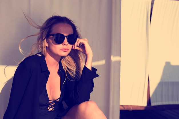 Jolie jeune femme blonde avec des lunettes de soleil dans le bungalow sur la plage au coucher du soleil