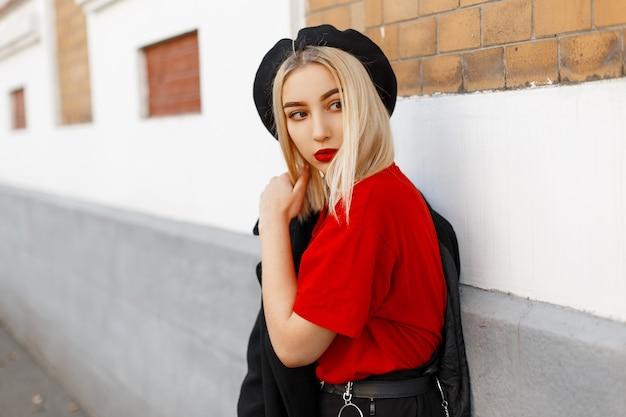 Jolie jeune femme blonde moderne à la mode avec des lèvres sexy dans un manteau noir à la mode dans un t-shirt rouge élégant dans un élégant béret se tient dans la ville près d'un bâtiment vintage