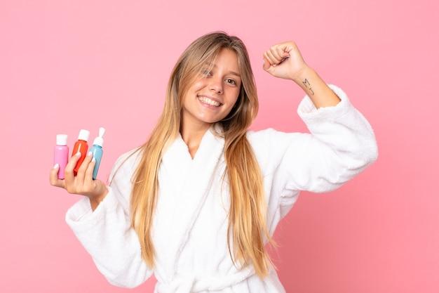 Jolie jeune femme blonde portant un peignoir et tenant un produit cosmétique