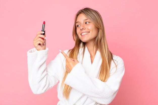 Jolie jeune femme blonde portant un peignoir et tenant un rouge à lèvres