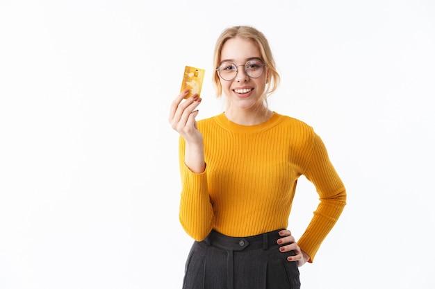 Jolie jeune femme blonde portant un pull debout isolé sur un mur blanc, montrant une carte de crédit