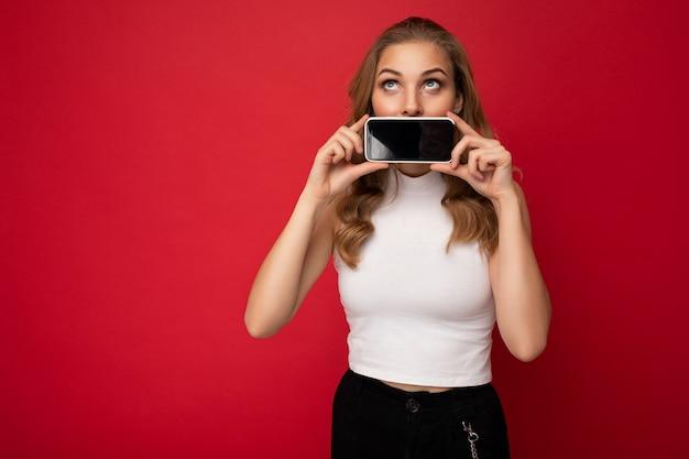 Jolie jeune femme blonde portant un t-shirt blanc isolé sur fond rouge avec espace de copie tenant un smartphone montrant le téléphone à la main avec un écran vide pour la découpe en levant.