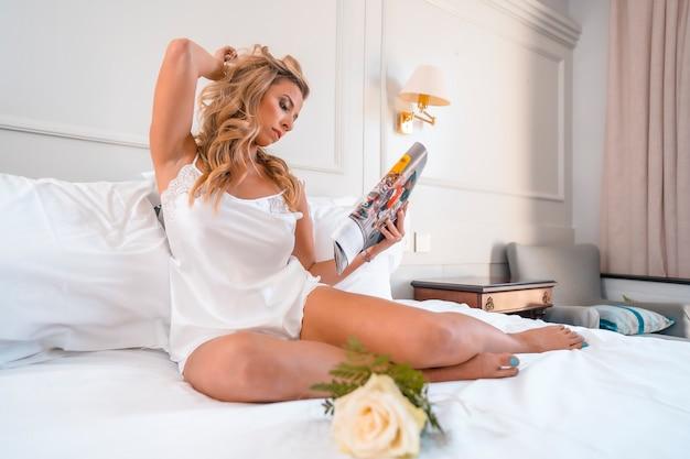 Jolie jeune femme blonde de race blanche en chemise de nuit dans un lit d'hôtel en lisant un magazine