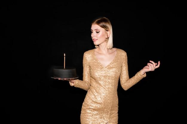 Jolie jeune femme blonde regardant bougie allumée sur le gâteau d'anniversaire recouvert de massepain noir tout en profitant de la fête dans l'obscurité