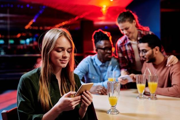 Jolie jeune femme blonde regardant à travers des photos ou des messages dans les réseaux sociaux sur smartphone alors qu'il était assis dans un café avec des amis