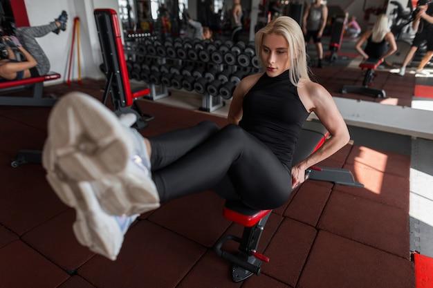 Jolie jeune femme blonde s'entraîne assis dans la salle de gym