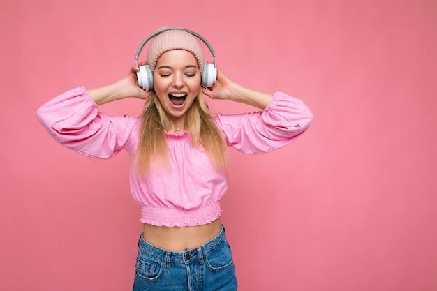 Jolie jeune femme blonde souriante émotionnelle positive portant un chemisier rose et un chapeau rose isolé