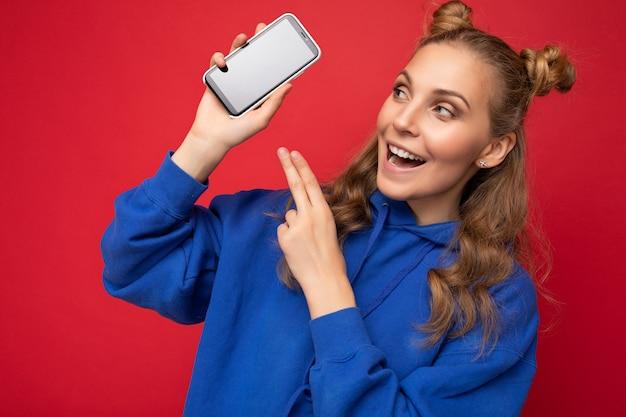 Jolie jeune femme blonde souriante portant un sweat à capuche bleu élégant isolé sur fond rouge avec