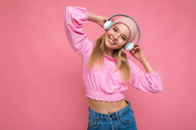 Jolie jeune femme blonde souriante positive portant chemisier rose et chapeau rose isolé