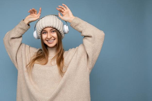 Jolie jeune femme blonde souriante positive portant un pull et un chapeau d'hiver beige