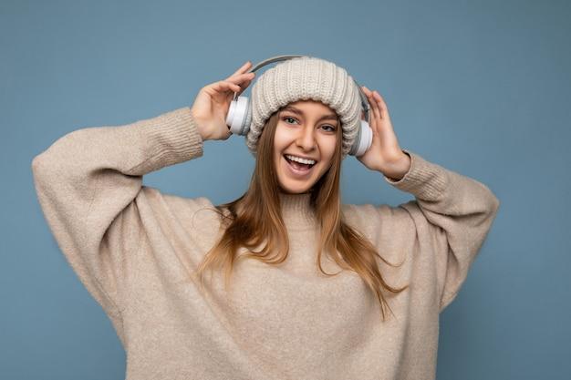 Jolie jeune femme blonde souriante et positive portant un pull d'hiver beige et un chapeau isolé sur