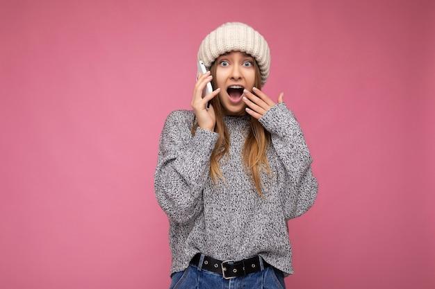Jolie jeune femme blonde surprise portant un pull gris décontracté et un chapeau beige isolé sur fond rose tenant dans la main et communiquant sur un téléphone portable en regardant la caméra avec la bouche ouverte.