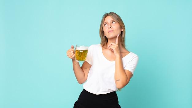 Jolie jeune femme blonde tenant une pinte de bière