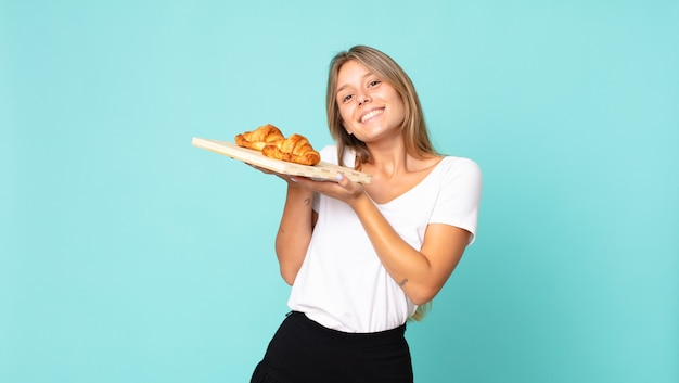 Jolie jeune femme blonde tenant un plateau de croissants