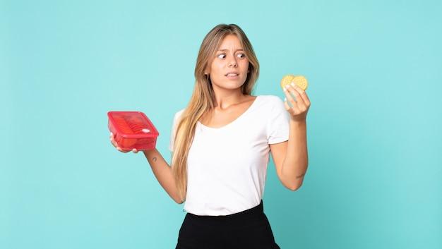 Jolie jeune femme blonde tenant un tupperware