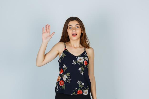 Jolie jeune femme en blouse agitant la main pour saluer et avoir l'air étonnée, vue de face.