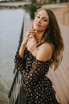 Jolie jeune femme brune aux cheveux longs, debout au bord de la rivière